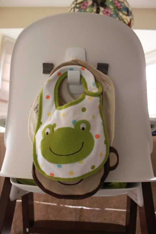 Stick a Command hook on the back of a high chair to hold bibs.