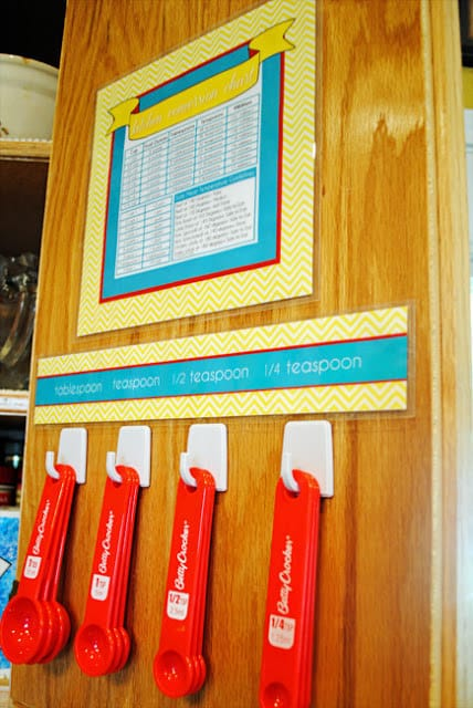 Use self-adhesive hooks to hold measuring items in a kitchen cabinet.