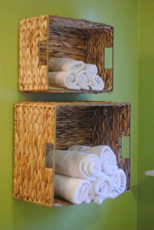 Hang baskets on the wall to hold towels in the bathroom.
