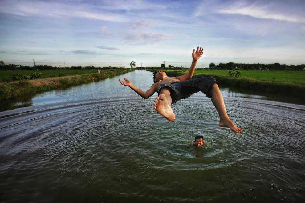 Boys jump into a river near Nghiem Xuyen village, Hanoi, Vietnam.