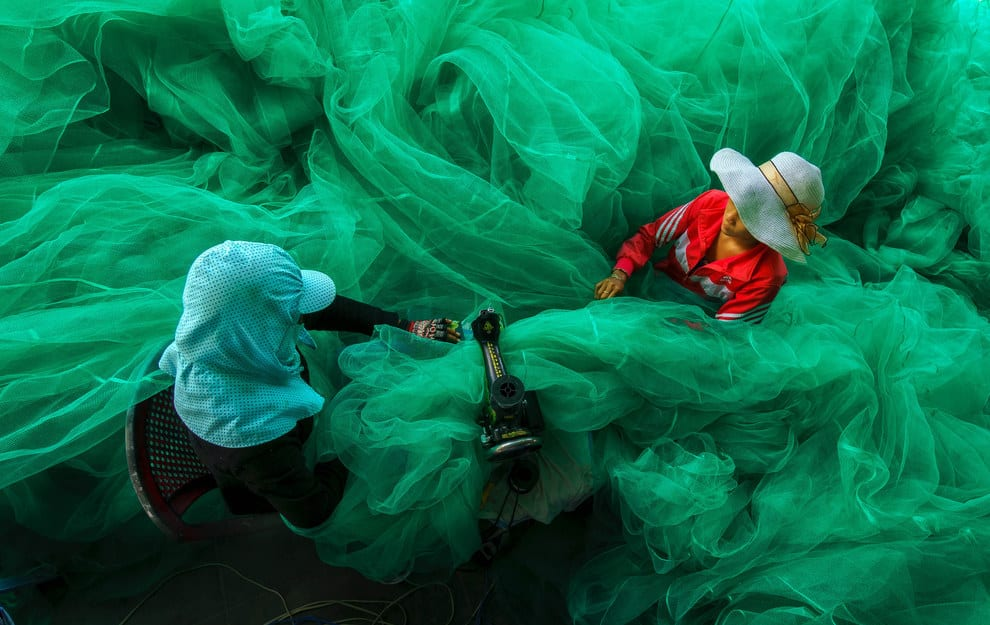 Women sew fishing nets in Vinh Hy Bay, Ninh Thuan, Vietnam.