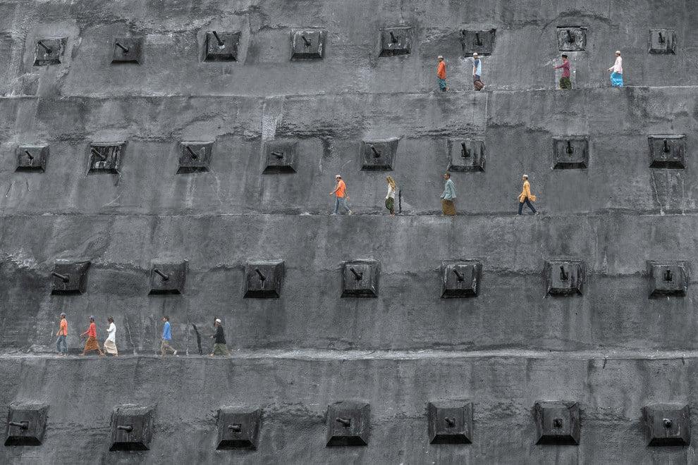 """Muslims walk along a retaining wall toward a mosque to pray"" in Kuala Lumpur, Malaysia."