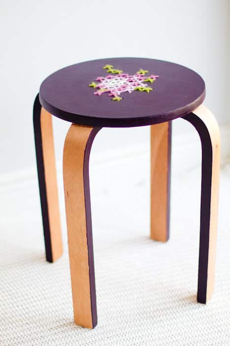 Cross-stitch a design on the top of a Frosta stool.