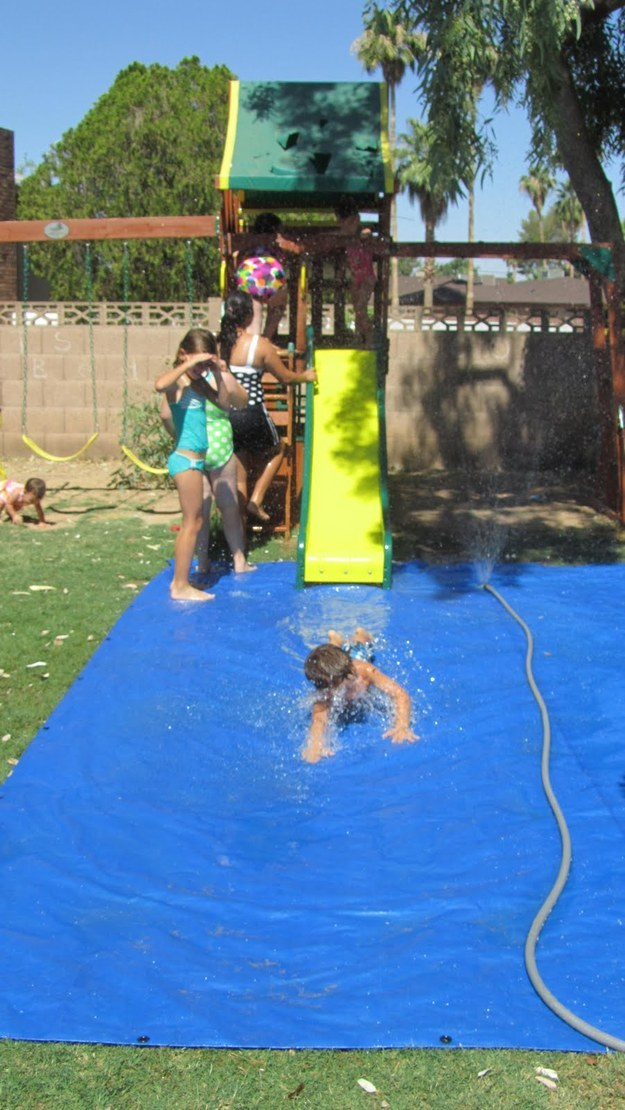 A tarp and sprinkler will create a fun splash pad for a slide.