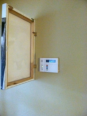Use a canvas on a hinge to cover an alarm panel or fuse box.
