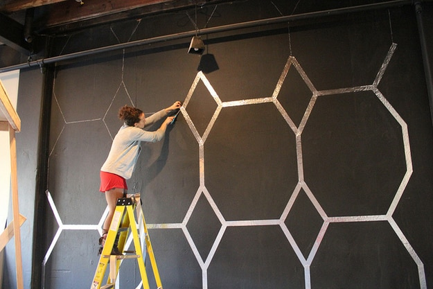 Use foil tape to create a wallpaper-like design on a wall.