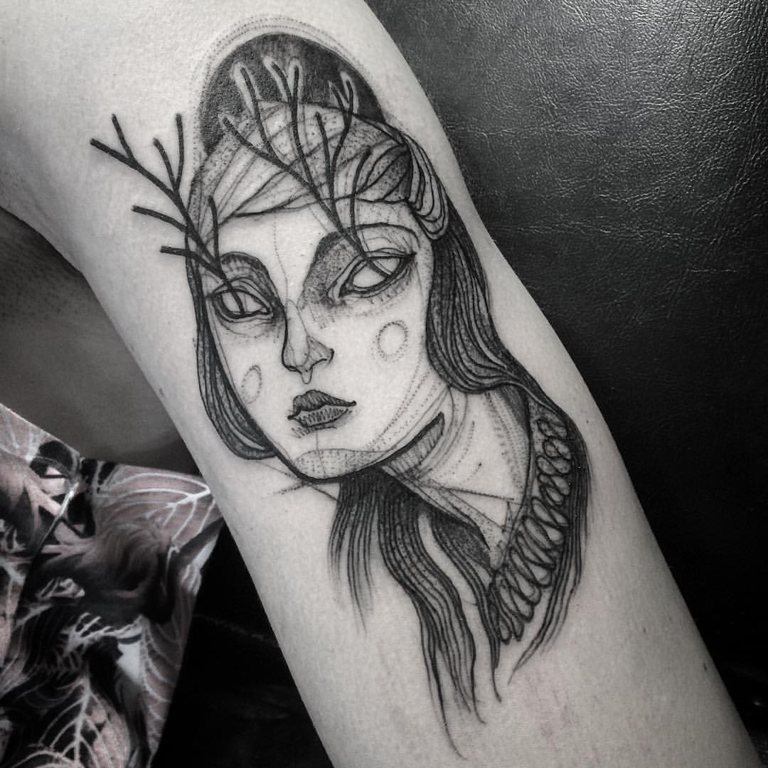 A pencil sketch tattoo of a woman with trees in her eyes