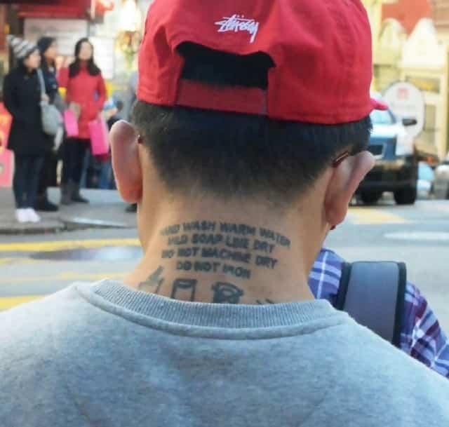 A man has a clothes washing label tattooed onto the back of his neck