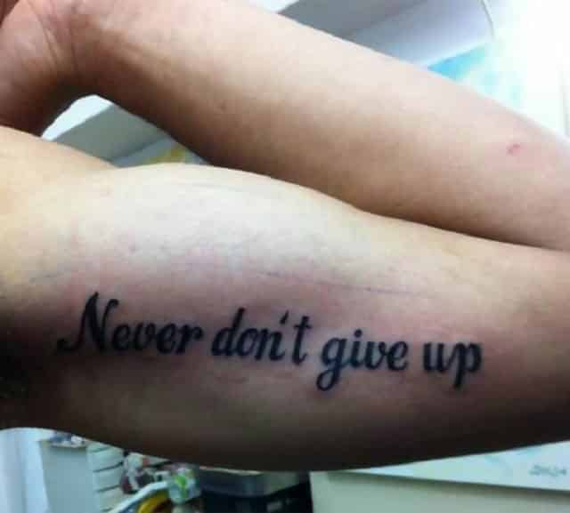 A man has had a tattoo on his bicep that says, 'Never don't give up'
