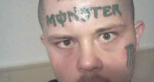 A man with a tattoo of the logo for the energy drink brand Monster on his forehead