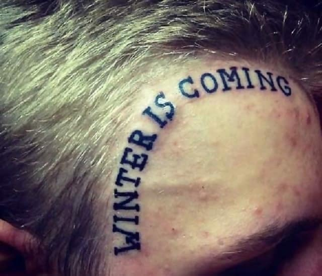 "A man with a tattoo on his forehead which says, ""Winter is Coming"""