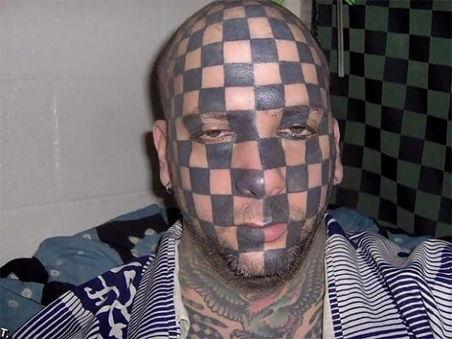 A man with a whole face tattoo which are black squares, creating a chessboard effect
