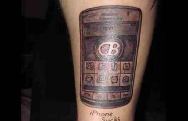 "A tattoo of a Blackberry phone with the writing ""iPhone sucks"" underneath"