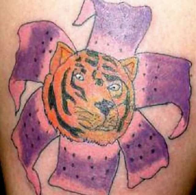 A tattoo of a tiger within a flower that is extremely badly drawn like it was done by a child