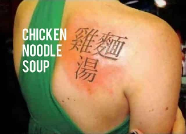 "A tattoo on a woman's back in another language, which translates to ""chicken noodle soup."""