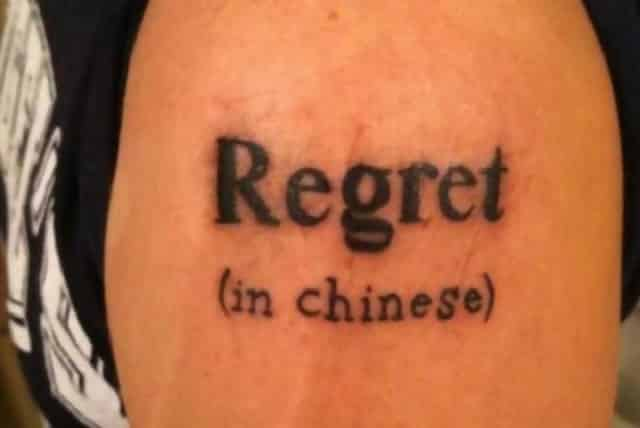 "A tattoo on someone which says ""Regret"" with ""(in Chinese)"" underneath"