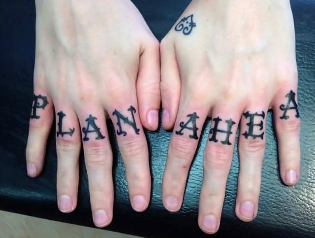 A woman has had the letters 'PLAN AHEA' on each finger but ran out of space for the 'D'