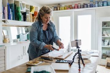 Female artist filming mosaic tutorial in home art studio