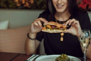 woman in black long sleeve shirt holding a burger